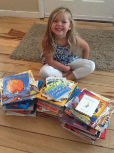 Girl smiling sitting in front of a stack of books